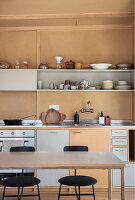 Simple kitchen in brown and grey with crockery in earthy tones