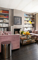 Two sofas opposite one another in front of open fireplace flanked by bookshelves
