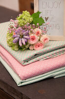 Bouquet on stacked folded fabrics in pink and mint green
