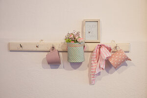 Fabric-covered basket of flowers and crockery hung from peg rack