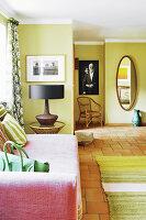 Rosafarbenes Sofa im grünen Wohnzimmer