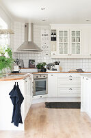 White fitted kitchen with corner cabinets and white wall tiles