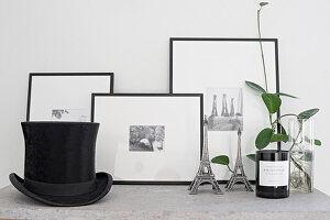 Grünpflanze, Eifelturm-Miniature, eingerahmte schwarz-weiße Fotos und Zylinder auf Ablage