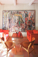 Wooden chairs, red sofa set and large artwork on wall in Mediterranean lounge