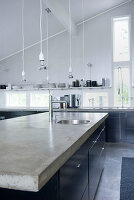 Concrete worksurface on island counter in front of tall narrow window