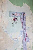 Garderobe aus Garnrollen an der Wand mit abblätternder Farbe
