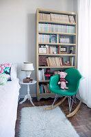 Grüner Designer-Schaukelstuhl vorm Bücherregal im Schlafzimmer