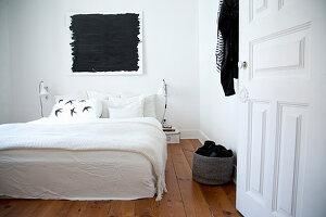 Doppelbett mit weißer Decke, darüber schwarzes Bild im Schlafzimmer mit Holzdielenboden