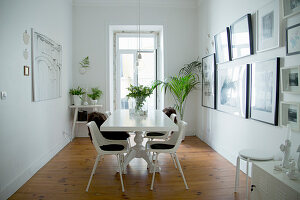 Houseplants in white dining room with collection of pictures on wall
