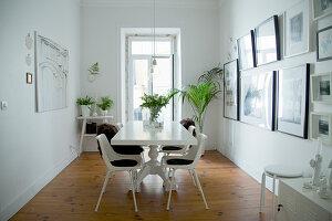 Weißes Esszimmer mit Grünpflanzen und mit Bildersammlung an der Wand