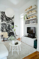 Round white side table on pale rug, TV cabinet, wall-mounted shelves and two chairs against large poster in living room