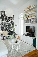 Runder, weißer Beistelltisch auf hellem Teppich, Fernsehschrank, Wandregale und zwei Stühle vor Wandposter im Wohnzimmer