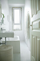 View into white bathroom with mosaic tiles