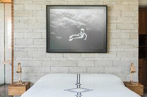 Doppelbett, darüber schwarz-weiße Fotografie, und Nachkästchen im Schlafzimmer