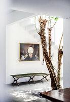 Feldbett, darüber Fotokunst, im Vordergrund Baum in der Eingangshalle