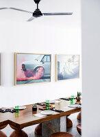 Gedeckter Tisch aus Teakholz und Hocker, Fotokunst an der Wand