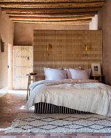 Bett an der Raumteilerwand im marokkanischen Schlafzimmer