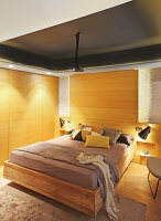 Pale wooden panels and fitted wardrobes in bedroom