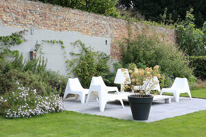 weiße Plastikstühle auf der Terrasse an der Gartenmauer