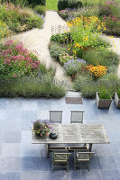 View down onto garden furniture on terrace adjoining herbaceous borders