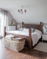 Selbst gebautes Holzbett, Nachtkästchen und Korbtruhe im Schlafzimmer
