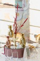 Verspiegeltes Podest mit Vase, Kerzen und goldener Ananas auf festlich gedecktem Tisch