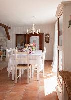 Festlich gedeckter Tisch mit Rosendekoration unter Kerzenleuchter im Essbereich