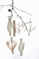 Pendants made from strips of paper hung from twig against white background