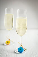 Colourful tags made from corks on two glasses of sparkling wine