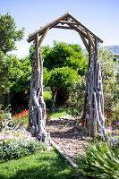 Gartenbogen aus Holz über dem Weg im exotischen Garten