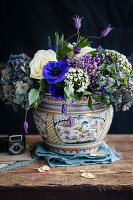 Arrangement of blue, purple and white flowers in china vase against black background