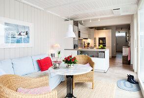 Sofa mit blauer Husse, runder Tisch und Rattansessel im Wintergarten, im Hintergrund offene Küche