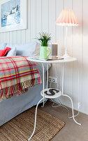 Filigraner Tisch mit Leuchte neben Bett im Schlafzimmer