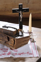 Old books, crucifix, rosary beads, glass and candle on wooden table