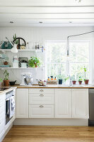 White-painted wooden walls and ceiling in country-house kitchen