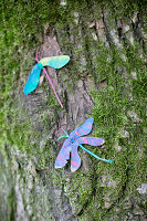 Dragonflies made from painted sycamore seeds on mossy tree