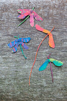 Dragonflies made from painted sycamore seeds on wood
