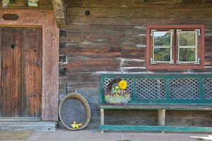 Autumn arrangement in basket with handle on wooden bench outside rustic wooden house