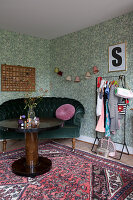 Runder Holztisch, Samtsofa und Kleiderständer vor grüner Tapete