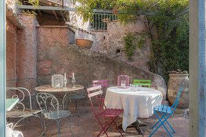 Bunte Gartenstühle und Tische im mediterranen Innenhof