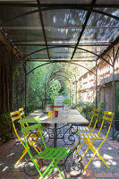 Colourful garden chairs around metal table on Mediterranean terrace