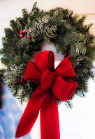Wreath of twigs with red ribbon in window