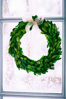Wreath of box leaves in window