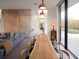 Long wooden table in open-plan interior next to glass wall overlooking terrace