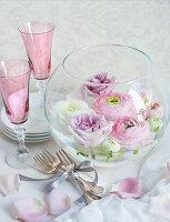 Hochzeitsdekoration: Glasschale mit Blüten, Sektgläser und Besteck auf einem Tisch