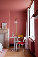 Small seating area next to disused fireplace in bedroom with salmon-pink walls