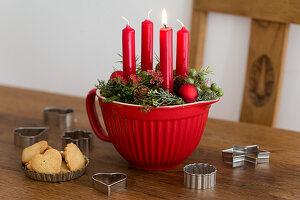 Vier rote Kerzen in einer Rührschüssel als Adventskranz