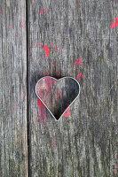 Herzförmige Ausstechform auf Holz mit roten Farbkleksen