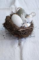 Osternest mit Deko-Eiern und Osterhäschen