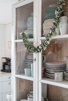 Garland of dried leaves on door of crockery cupboard